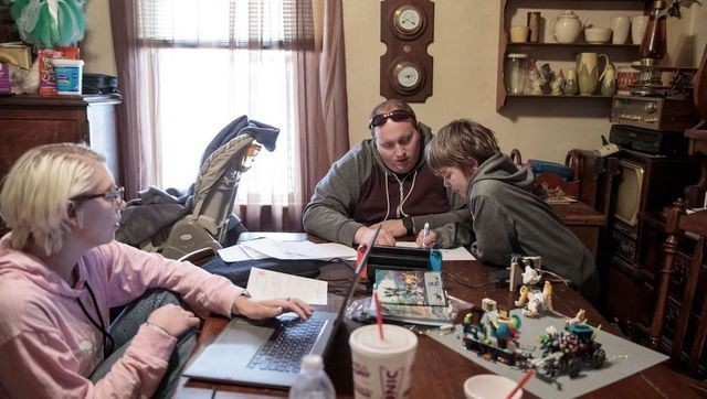 Sarah and Joshua Fuller help their son, Brendan, with a school project. The family moved in with Sarah's parents on Christmas Eve.